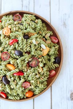 A delicious vegan pesto gluten free pasta salad with chickpeas, basil, tomatoes, olives and nuts that is perfect for a healthy Summer potluck or picnic.