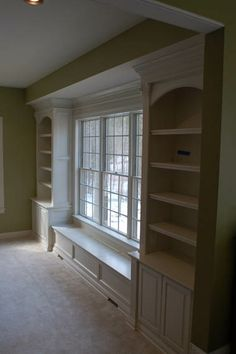 Bookshelves and window seat built around a large window