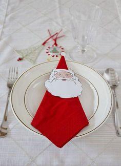 serviette rouge en forme de triangle décorée d'un dessin le visage de père Noël en papier