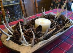 red flannel plaid tablecloth, dough bowl centerpiece with pine cones, antlers and candle.