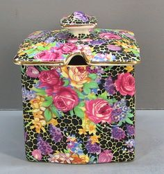 """Royal Winton, Grimwades, """"Hazel"""" Pattern English Chintz Covered Jam Jar Pot. This Hazel pattern Chintz jam pot is about 2 ½"""" square and 2 ½"""" deep with a 2 ¾"""" square cover that has a notch on one side for a spoon handle. The Hazel chintz pattern has pink and yellow roses with smaller purple flowers on a black background with a white netting design. The edge of the cover and rim of the pot are trimmed with gold."""