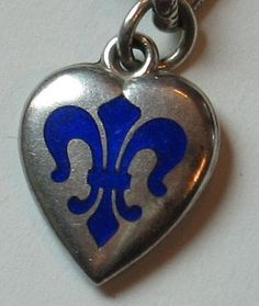 Stunning enamel work on this beautifully simple fleur-de-lis puffy heart...