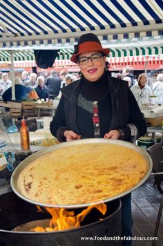 THERESA, THE SOCCA QUEEN IN THE COURS SALEYA MARKET IN NICE. SOCCA is a thin pancake made of chickpea flour and olive oil, baked in a huge plaque in an 900° oven until brown and crispy. It is scraped off and eaten sprinkled with lots of black pepper.
