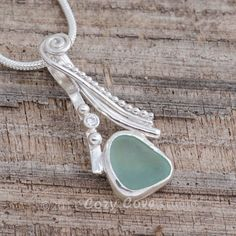 Sea glass pendant necklace crafted from soft green sea glass accented with a sparkly CZ in a handmade sterling silver setting. #artisanjewelry #metalworkjewelry