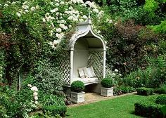 Classic gazebo with bench and cushions in formal garden. Rosa 'Kiftsgate', Teucrinum, Cotinus, Buxus sempervirens - Box topiary balls - Image No: 0074131 - GAP Gardens, garden and plant stock photography
