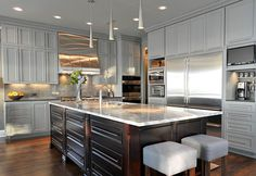 Grey kitchen cabinets with espresso stained island.
