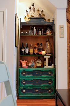 """Liz's Exuberant Row House via Apartment Therapy.  Love the clear wine holders above """"traditional"""" furniture"""
