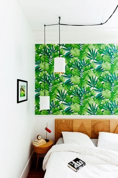 Small bedroom with green botanical wallpaper and wooden headboard.
