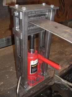 Bracket Press - Homemade bracket press used for reproducing vintage parts. Constructed from steel tubing, steel plate, flat bar, a bottle jack, and nuts and bolts.