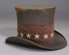 Patriotic Parade or Campaign Top Hat, America, late 19th century, the hat painted gray blue, woven cotton red band with thirteen applied white stars, (paint wear, fading), ht. 8 in. sold for $1400