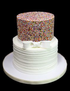 A two tiered wedding cake with colorful Nonpareil Sprinkles and Horizontal Old-Fashioned Buttercream with a White fondant bow.