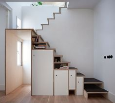 Plywood staircase by Buj+Colón Arquitectos integrates shelves and cupboards for a small flat: A plywood staircase with built-in cupboards and bookshelves frames a doorway in this Madrid apartment Space Saving Staircase, Staircase Storage, Stair Storage, Staircase Bookshelf, Iron Staircase, Bookshelf Storage, Plywood Interior, Interior Stairs, Interior Architecture