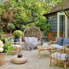 Gravel patio area with rattan table and chairs. Potted olive trees and hydrangeas help add to the landscaped but bohemian garden vibe. - All For Garden Gravel Patio, Backyard Patio, Pergola Patio, Potted Olive Tree, Bohemian Patio, Bohemian Garden Ideas, Bohemian Decor, Def Not, Small Patio