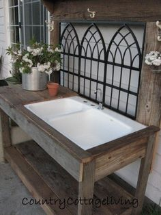 How this idea can work for me:  decorative fence/recycled iron piece for back board/tool rack. Recycled sink w/ a hose connection. What a great potting bench!