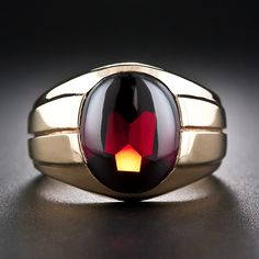 Here's one we've never seen before: an original vintage Tiffany & Co. gent's ring highlighting an unusual buff-top garnet (faceted on the bottom and cabochoned on top). The bold and weighty ring is substantially crafted in sturdy 14 karat yellow gold with a striking fluted design continuing all around the ring shank. Circa 1950s (we think) 5/8 inch high.