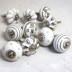 Set of 10 Grey White Black Silver Vintage Cupboard Knobs as shown in the picture. Includes a mixture of black, grey, silver and white cupboard knobs. Update your interior with these stunning ceramic vintage door knobs adding style to your furniture. Brighten up your kitchen cupboards, Transform you bedroom wardrobes and provide that perfect finishing touch.  Description: Code:               PKS34Quantity:          1 pack of 10 knobsStyle:               Black,%