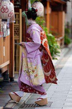 Junior maiko; notice her long kanzashi silk strands. The lanturns have the symbol of one of the geisha districts in Kyoto; Miyagawa-cho.
