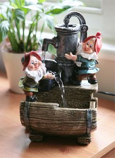 Garden Helpers Pump and Barrel Water Feature with LED Light - H28cm   Enjoy the delightful water display of the two woodland gnomes pouring water from the pump into a wooden barrel. Illuminated by an enhancing LED, it makes a charming addition to any garden.      Feature