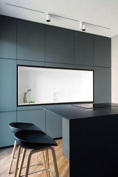 une cuisine d'esprit minimaliste en blanc et couleur canard qui tire vers le gris, îlot central noir au design épuré