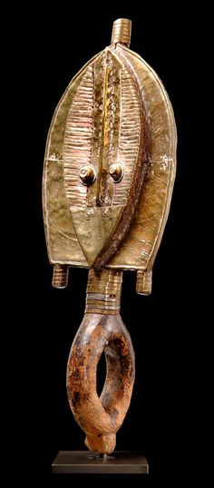 Africa   Reliquary figure from the Kota-Shamaye people of Gabon   Wood and hammered brass sheet    Representing the southern style of Kota reliquaries, the type of the Shamaye. Characteristic is the tapering face, by the long vertical nose ridge nearly subdivided into two parts, and the simple coiffure.