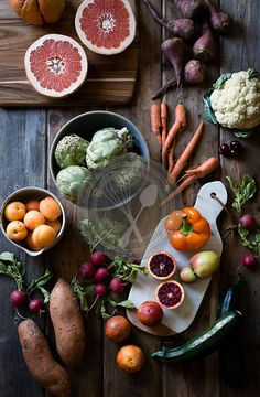 Fruit and vegetables laid out on a farm table. Carrots, cauliflowers, beets, peaches, oranges.