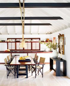 [Room] Simple dining area with a vaulted ceiling, plantation shutters and a large teak and oak dining table in this home located in Saint-Barthélemy. Oak Dining Table, Dining Area, Dining Room, Kitchen Dining, Kitchen Counters, Room Kitchen, Wood Table, Style At Home, Elle Decor