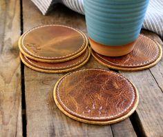 Fair Coasters are hand made in Chicago using rich pull-up leather, a cork base, and upholstery-strength thread.   The leather is stamped with the Fair Coast logo and the cork base is hand-painted with gold or copper detailing.   A fine, functional resting pad for your cup or glass. Available in-store & online.