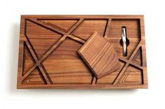 """""""The Puzzle"""" wine tray, named after Newton's icon blend, combines 10 removable puzzle pieces that can be popped out to serve as coasters or smaller, individual serving trays for fruits, nuts, cheese and other wine-paired snacks. Each of the 112 pieces is handcrafted from responsibly sourced walnut wood, reflecting the eco-conscious ethos of the winery"""
