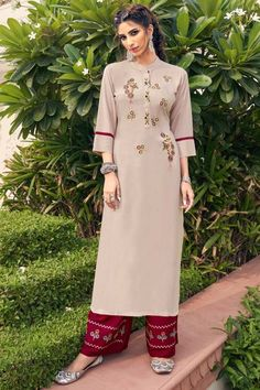 Look elegant when wearing this beige rayon trouser suit which makes it astonishingly charming. This collar neck and 3/4th sleeve party wear attire elaborated using resham work. Matched with rayon palazzo pant in dark maroon color with dark maroon chiffon dupatta. Palazzo pant has resham work. Dupatta elaborated using plain work. #trousersuit #salwarkameez #malaysia #Indianwear #Indiandresses #andaazfashion Trouser Suits, Trousers, Palazzo Suit, Kurta Palazzo, Beige Color, Maroon Color, Women Salwar Suit, Beige Dresses, Dress Suits