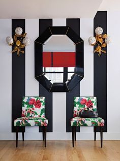 entry vignette bold black and white stripe walls with colorful chairs and interesting flower sconces that look retro