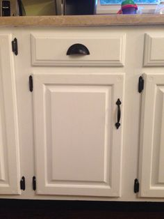 We painted the existing oak cabinets white and replaced hardware with black cup  pulls and handles