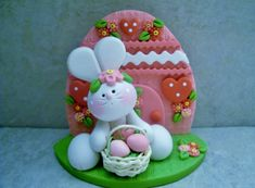A little bunny is holding a tiny basket that contains three eggs. He is seated in front of a decorated Easter egg shaped house!  This is an original design thats been handcrafted from polymer clay. The piece stands approximately 3 tall and all parts have been secured with liquid polymer for increased strength.  Not a toy...not suitable for young children.