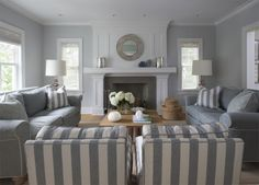 [living room] bold stripes in the accent upholstery -- could just be pillows. porthole-style mirror above the fireplace -- whimsical and coastal without being beachy-cute.