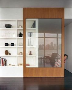 Sliding bookcase door made out of light colored wood, perhaps this is an ideal solution when looking to divide a 1970's lounge dining room. The large glass panel gives great privacy without blocking out light.: