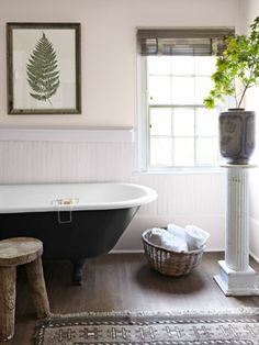 Need to give your bathroom and extra oomph? A dark coat of paint lends gravitas to a simple claw-foot tub. #bathrooms #decoratingtips