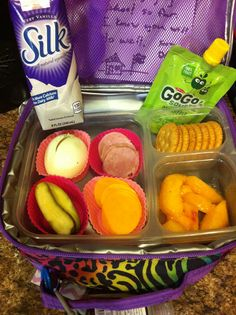 Turkey, cheddar, wheat ritz homemade lunchable with boiled egg, pickle, fresh peach and applesauce pouch