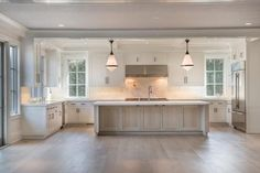 gorgeous white kitchen with light  wood floors. totally fixer upper style redo. love the big kitchen island