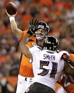 Denver Broncos quarterback Peyton Manning (18) throws under pressure from Baltimore Ravens outside linebacker Daryl Smith (51) during the second half of an NFL football game, Thursday, Sept. 5, 2013, in Denver. (AP Photo/Joe Mahoney)