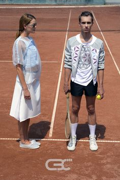 Lookbook:  Him: White tshirt, grey bomber jacket, black shorts. Her: Blue top, sheer tshirt, white midi skirt. Tennis court, sport, sportswear, fitness, trends, unisex, campaign photos. Order via facebook, pm or e-mail.