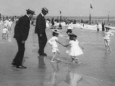Coney Island, Brooklyn, NYC 1900; SUCH GOOD DADDIES--OUT THERE IN THE SAND AND SALTWATER WEARING THEIR DRESS SHOES SO THEIR CHILDREN CAN HAVE FUN AT THE BEACH.