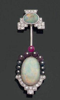 CARTIER. Broche en or gris ornée d'opales dans un entourage de diamants de taille huit-huit et de saphirs, rubis et améthystes cabochons. photo Aguttes (BB)