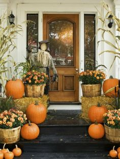 pumpkins and hay with orange mums on front steps