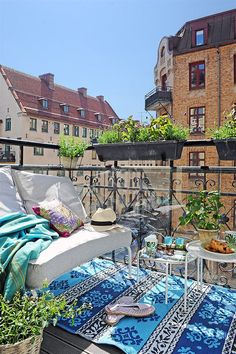 A tiny city balcony with blue outdoor mat rug aqua throw and simple white furniture. A little boho, a little eclectic, fresh and happy.