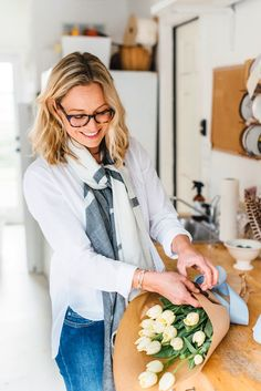 Kim Curtis of Toast arranges tulips, wearing jeans and top from Jenni Kayne and a handmade Indian cashmere scarf from Whistle Club. Photo by Cara Robbins. Styled by Judy Foreman. http://sbseasons.com/2016/03/style-file-spring-style-with-kim-curtis/ #sbseasons #sb #santabarbara #SBSeasonsMagazine #ToastSantaBarbara #WhistleClub #SBStyle #JenniKayne #KimCurtis #CaraRobbins #SantaBarbaraStyle #SeasonsSpringStyle #JudyForeman To subscribe visit sbseasons.com/subscribe.html