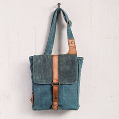 """Carry your tech gear in style with the Ashton Tech Bag, especially when all you need is your tablet. Features denim canvas with a darker denim canvas flap and snap to secure the bag, genuine leather and antique metal hardware accents with a 25"""" adjustable shoulder strap. Bag measures 10""""W x 8.5""""H x 2""""D. #monab #denim #upcycled #tote #bag"""
