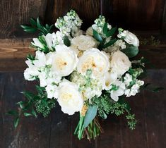 The bride will carry a slightly asymmetrical bouquet of cream hydrangeas, ivory garden roses, white stock flowers, white freesia, ivory spray roses, seeded eucalyptus, and Italian ruscus wrapped in ivory ribbon