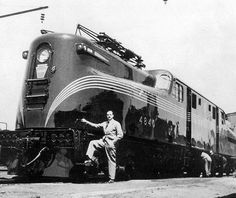 Raymond Loewy stands next to his masterpiece, the GG1.