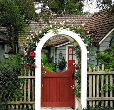 Beautiful arbor entry enclosed with a red gate and covered in pale pink and red climbing roses
