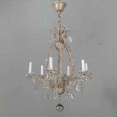Pair Italian Chandeliers With Round Beads and Original Beaded Canopies  --  Pair circa 1900 Italian six light chandeliers with frames covered in clear, flower-shaped crystal beads, cut crystal bobeches, candle style lights, large crystal prisms and center drops. Original metal ceiling canopies with beaded details. New electrical wiring for US standards. Sold and priced as a pair.  --   Item:  7053  --  Price:  $6495