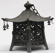 """Description: Japanese bronze hanging lantern, of hexagonal form on six supports with openwork side panels including a hinged door, with a wave pattern on the roof, each corner of the roof with a bell, the finial with a handle and linked to an iron chain (one bell is missing), 10.5""""h"""